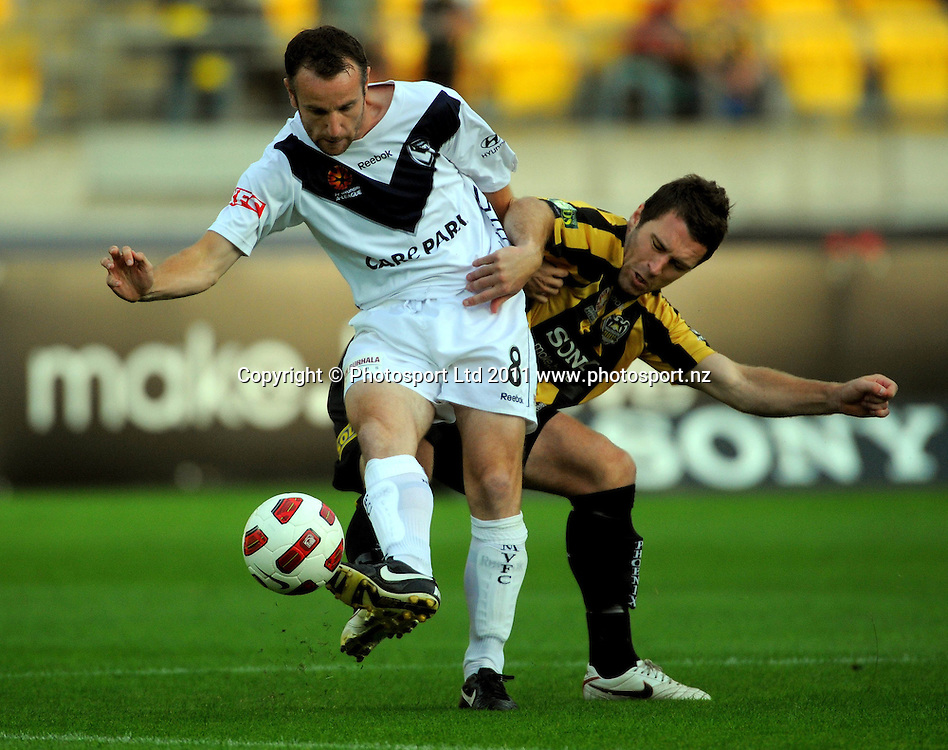 Victory's Grant Brebner gets his pass away under pressure from Tim Brown. A-League football - Wellington Phoenix v Melbourne Victory at Westpac Stadium, Wellington, New Zealand on Wednesday, 5 January 2011. Photo: Dave Lintott/PHOTOSPORT