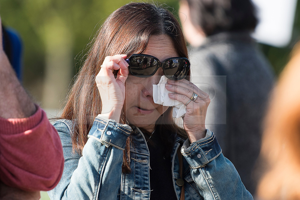 © Licensed to London News Pictures. 31/08/2017. London, UK. An emotional woman wipes a tear from her eye while looking at flowers and tributes left at the gates to Kensington Palace in London on the 20th anniversary of the death of Diana, Princess of Wales. Princess Diana was fatally injured in a car crash along with her companion Dodi Fayed, while the couple were being driven through the Pont de l'Alma tunnel in Paris on 31 August 1997. Photo credit: Ben Cawthra/LNP