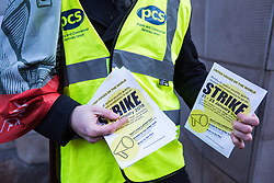 London, UK. 22nd January, 2019. A member of the Public and Commercial Services (PCS) union hands out leaflets outside the Ministry of Justice (MoJ) as receptionists, security guards and cleaners there represented by the United Voices of the World (UVW) trade union begin a strike for the London Living Wage of £10.55 per hour and parity of sick pay and annual leave allowance with civil servants. The strike is being coordinated with support staff at the Department for Business, Energy and Industrial Strategy (BEIS) from the Public and Commercial Services (PCS) union.