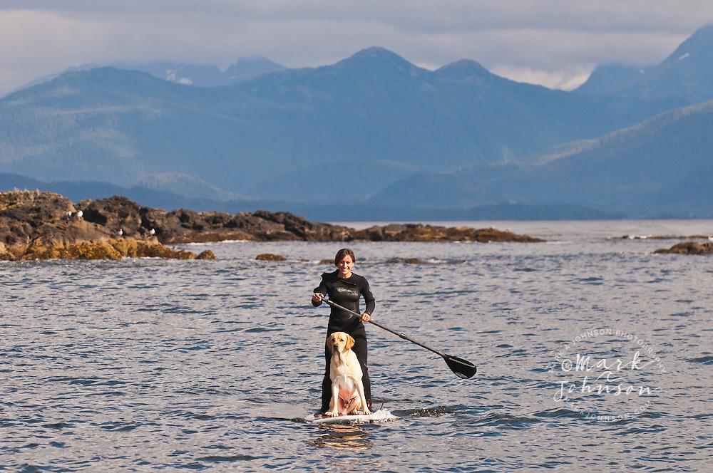 Woman & dog Standup Paddle Boarding off Kruzof Island, Southeast Alaska
