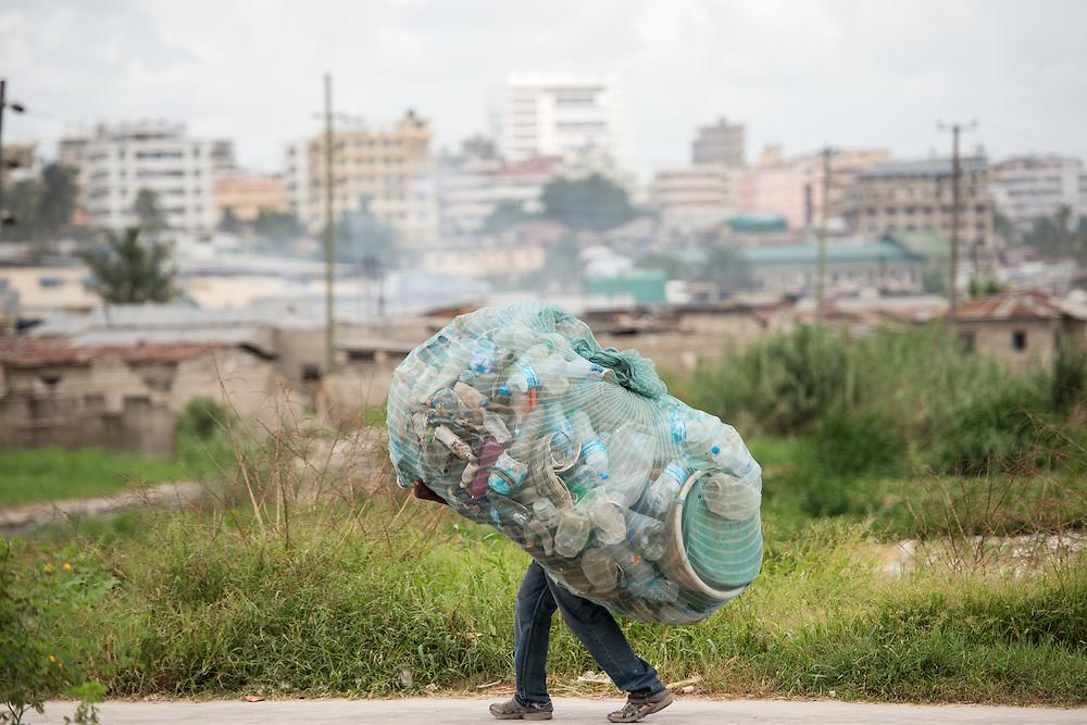 Dar es Salaam, Tanzania - 2015-05-24 - A man carries a load of recyclables in Dar es Salaam, Tanzania on May 24, 2015.  Photo by Daniel Hayduk