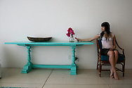 Woman holding purple bugambilia flower, sitting next to turquoise table.<br />