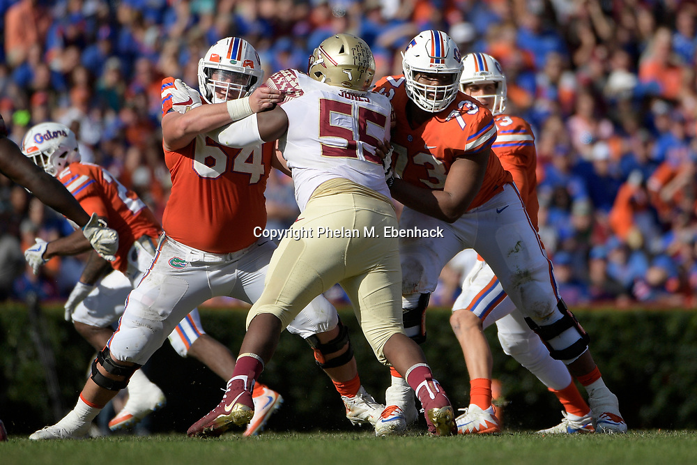 Florida offensive lineman Tyler Jordan (64) and offensive lineman Martez Ivey (73) block against Florida State defensive tackle Fredrick Jones (55) during the second half of an NCAA college football game Saturday, Nov. 25, 2017, in Gainesville, Fla. FSU won 38-22. (Photo by Phelan M. Ebenhack)