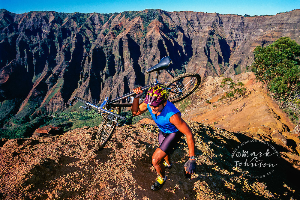 Man carrying his Mountain bike up a ridge, Kauai, Hawaii
