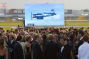"Prince Albert of Monaco (m). having fun while the Flying Bull's vintage ""Corsair"" fighter plane passes on a video wall..2000 V.I.P.s paid 500 Euros each to view the spectacle from close and to enjoy catering by Cook of the Century, Eckart Witzigmann. All revenues went to charities, such as Queen Silvia of Sweden's cancer project..Hangar-7, the spectacular new home of the Flying Bulls (""Red Bull"" owner Didi Mateschitz' collection of classic airplanes), opens with aeronautical highlights like Karlheinz Stockhausen's ""Helicopter String Quartet"", a production of the Salzburg Festival, and ""Taurus Rubens"", a spectacular Theater for Flying Machines."