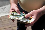 Man counting New Israeli Shekel banknotes