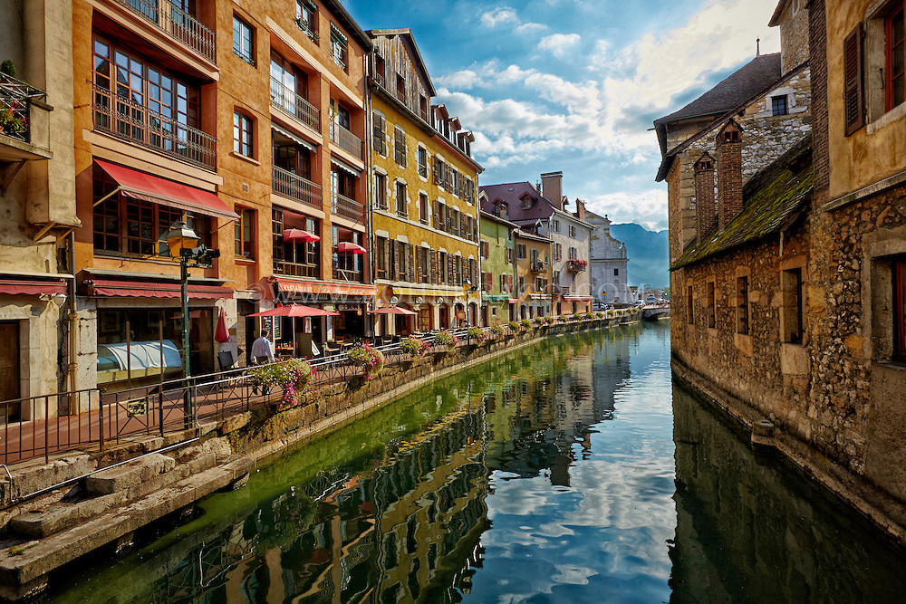 View of The French Alps, and colorful buildings along the reflective waters of Thiou Canal, Old Town Annecy, France.