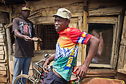An ex street boy from the Kiandutu slum buys meat from the local butcher. Since leaving the street he has become a Boda Boda (bicycle taxi) driver. Kiandutu is the largest slum in Thika, Kenya.