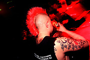 Gentleman with bright red mohican, tattoos on arm and hairey back, Capdown at The Forum, Kentish Town, London, U.K, 2000's.