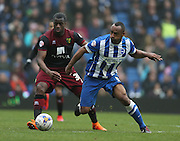 Chris O'Grady, Brighton striker beats Norwich City's defender Sebastien Bassong during the Sky Bet Championship match between Brighton and Hove Albion and Norwich City at the American Express Community Stadium, Brighton and Hove, England on 3 April 2015.