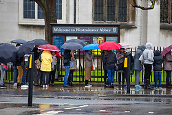 © Licensed to London News Pictures. 30/04/2018. London, UK. People brave the rain beneath umbrellas as they queue for Westminster Abbey in London as wet weather hits the United Kingdom. Photo credit: Rob Pinney/LNP