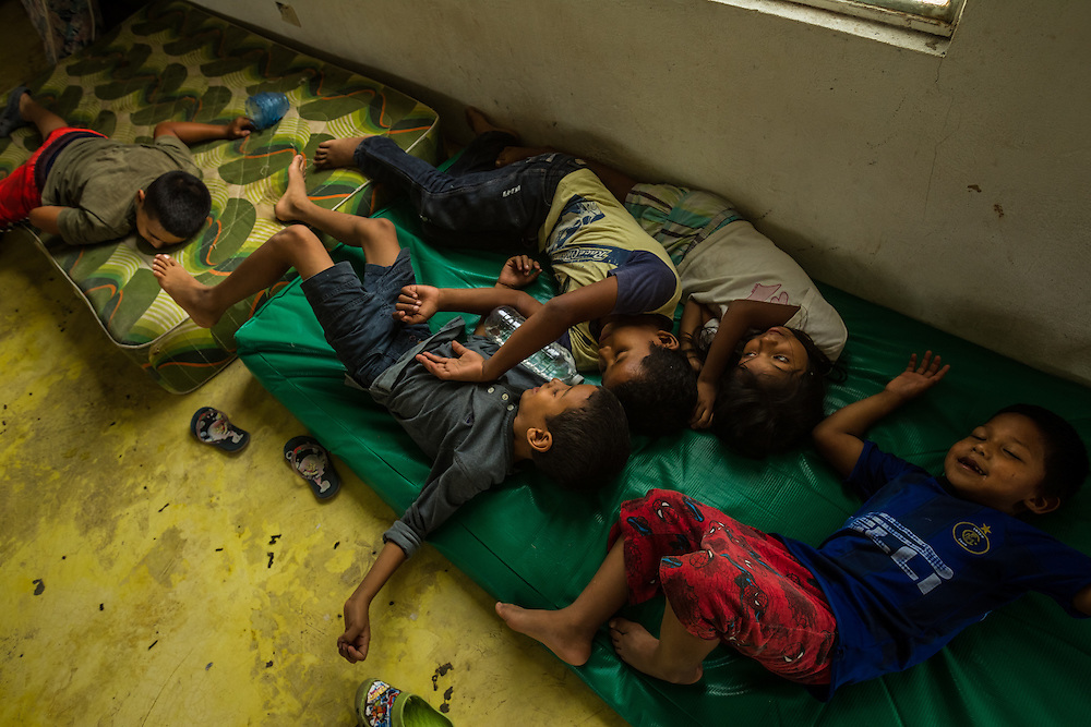 "TENOSIQUE, MEXICO - JULY 2, 2014: Undocumented migrant children play dead after being ""killed"" during a game of ""kidnappers"" at the 72 migrant shelter in Tenosique.  Many families and chilren migrating illegally to the United States are fleeing gang-violence in their home countries.  PHOTO: Meridith Kohut for The New York Times"