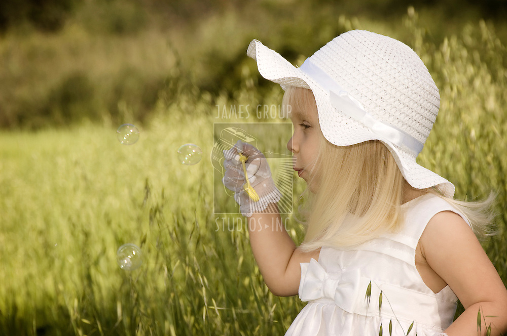 Little girl in a white dress and hat blowing soap bubbles in a field