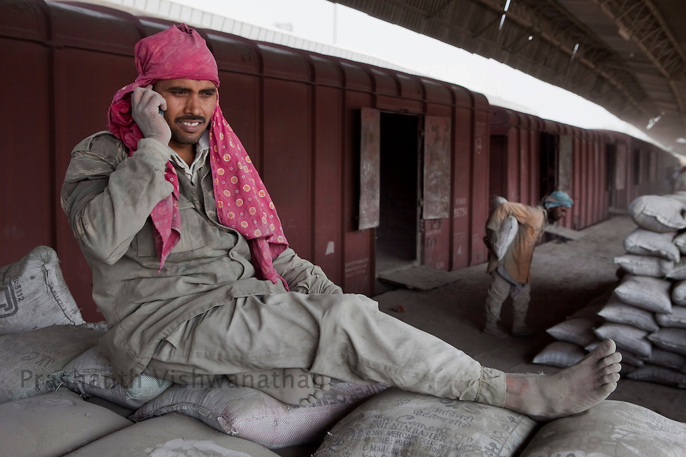 A labourer speaks on a phone sitting on cement bags even as other labourers unload  bags manually from freight trains at the Shakur Basti station in New Delhi, India, on Tuesday April 5, 2011.  Photographer: Prashanth Vishwanathan/Bloomberg News