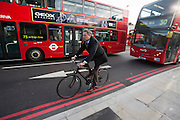 Een man fietst tussen de bussen in Upper Street in de Londense wijk Islington.<br /> <br /> A man is cycling between busses at the Upper Street in London area Islington.