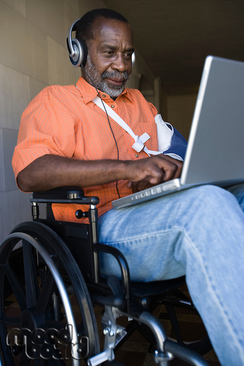 Elderly man in wheelchair listening to music and using laptop