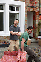 Two men with sofa outside house