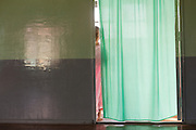 One young shy nun in pink, hiding behind green curtain, Compassion and Peace Nunnery, Inle Lake,  Nyaung Shwe