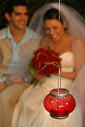 glass lantern with burning candle in front of an out of focus bride and groom