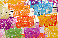 Brightly colored cut paper flags (known as 'papel picado') with Day of the Dead designs in Oaxaca, Mexico.