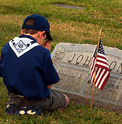 "Photo by Phil Grout..Cub scout John Henry Saurusaitis of Lineboro pauses to pray.at the graveside of army veteran Tec5 Forrest L. Johnson .after planting an American flag at the grave.  Later, scout.Sarusaitis said he prayed, ""because it was the first flag today.and I just wanted to honor him.""  Saurusaitis and his fellow scouts.of Pack 320 honored deceased veterans at the Old Lutheran Cemetery.in Manchester as well as the Immanuel Lutheran Church cemetery.as part of Memorial Day observance."