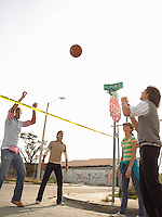 Friends playing volleyball over police tape in street