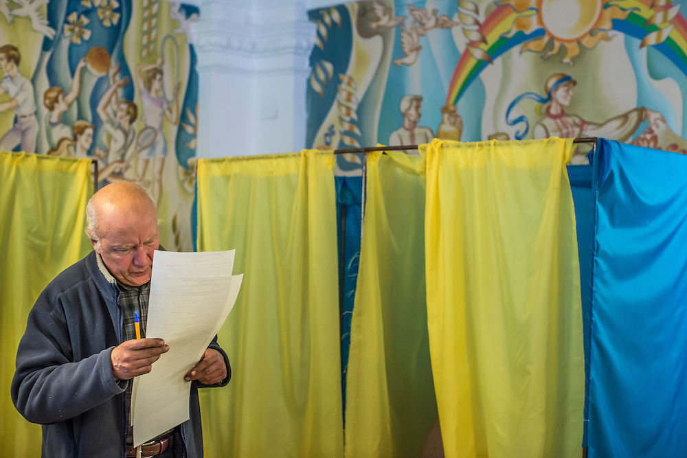 KIEV, UKRAINE - OCTOBER 26: A man reads over his ballot before voting in parliamentary elections on October 26, 2014 in Kiev, Ukraine. Although a low turnout is expected in the east of the country amid continued fighting between Ukrainian forces and pro-Russian separatists, Ukraine is expected to elect a pro-Western parliament in a further move away from Russian influence. (Photo by Brendan Hoffman/Getty Images) *** Local Caption ***