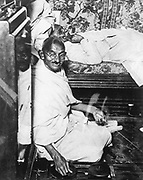 Mohondas Karamchand Gandhi  (1869-1948), known as Mahatma (Great Soul). Indian Nationalist leader. Here he is working at his spinning wheel, a symbolic task he performed almost daily.
