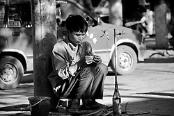 China, Xi'an, 2007. Sitting out the summer heat in Xi'an, an artisan creates beautiful butterflies and grasshoppers out of wet, green palm fronds..