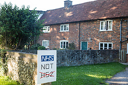 A sign calling for investment in the NHS rather than HS2 is displayed outside a house on 17th July 2020 in Great Missenden, United Kingdom. Local residents and environmental activists continue to campaign against the high-speed rail link, primarily on the grounds of its impact on the environment and cost.
