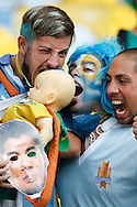 Uruguay fans pretent to bite a baby mimicking Luis Suarez who has been banned for biting in the game against Italy. Seen before in the stadium before the 2014 FIFA World Cup last 16 match at Maracana Stadium, Rio de Janeiro, Brazil.<br /> Picture by Andrew Tobin/Focus Images Ltd +44 7710 761829<br /> 28/06/2014