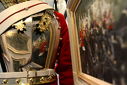 © Licensed to London News Pictures. 20/04/2012. London, UK . The painting Queen's Life Guard Band, Changing of the Guard by Katie Scorgie is selected in a soldiers breast plate. A Preview of the Household Cavalrys 'The Best of British' art exhibition. Soldiers walk around the artwork as they prepare to mount duties at Horse Guards Parade. The Queen's Life Guard are inspected before they depart the Barracks for the daily Guard change at 1100. The exhibition runs between 23 - 26 April. Hyde Park Barracks, Ceremonial Gate, South Carriage Drive, London, SW7 1SE. Photo credit : Stephen Simpson/LNP