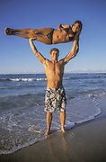 Australia, Queensland, N. Stradbroke Island, man holding woman above his head. people ****Model Release available