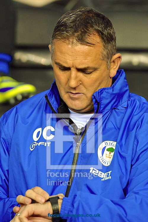 Picture by Ian Wadkins/Focus Images Ltd +44 7877 568959<br /> 28/11/2013<br /> Wigan Athletic manager Owen Coyle checks his watch ahead of the UEFA Europa League match at the DW Stadium, Wigan.