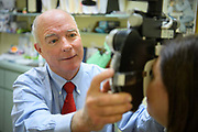 A Doctor of Optometry examines the eyes of a patient in an office setting.