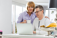 Mature couple using laptop together at table in house