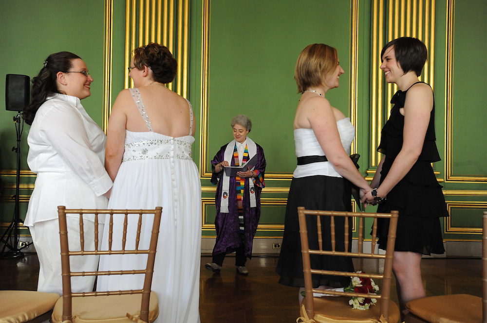 "Jessica Miller, 32,  Felicia Hurley, 25,  Kelly Thompson, 31, and Naomi Swickard, 28, hold hands as they wait for Rev. Bonnie Berger to pronounce them wife and wife. Ten couples participated in a mass same-sex wedding at the Andrew W. Mellon Auditorium in Washington, DC. The ""Our Time Has Come"" event was intended to serve as a symbol of gay equality."