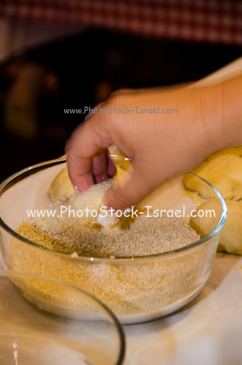close up of the Hands of a female pastry chef as she demonstrates how to  knead dough at a baking workshop. Dipping the dough in sesame seeds