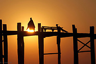 Sihilouettes at sunset on the U-Bain bridge in Myanmar.<br />
