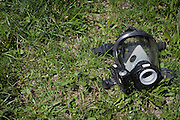 A gas mask rests in the grass across from the scene of a three-building fire on Bartlett Street in Lewiston, Maine on May 6, 2013. The fire was the third multi-building fire within three blocks this week.