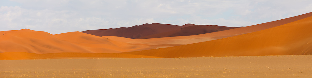 Cloud shadows play across a huge field of sand dunes, bringing out many different hues of orange and red, Namib-Naukluft National Park, Namibia.