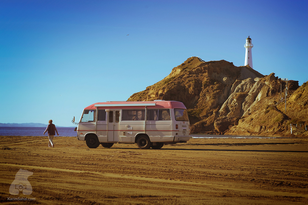 A camping van is parked on the beach near the lighthouse. Castlepoint, Wairarapa, New Zealand.