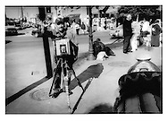 Photographer with an ancient view camera makes portrait along Tijuana's famous Avenida Revoluccion while women in background sells flowers and souvenirs to daytrippers from the US, Tijuana, Baja California, Mexico.  Tourism plays an important role in Tijuana's economy.