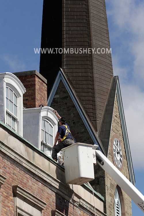 Middletown - A worker on a lift paints the windows on the roof of a building in downtown Middletown on May 23, 2008.