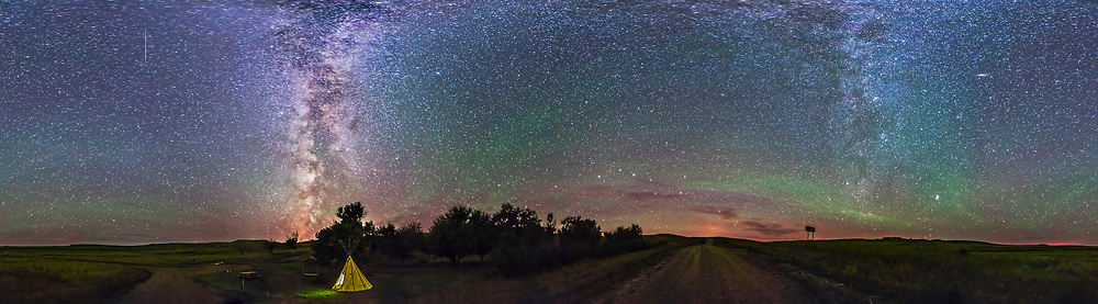 A 360&deg; panorama and more than 100&deg; from the ground to the zenith, taken at the Riverwalk picnic area in Grasslands National Park, Saskatchewan, August 25, 2014. Sagittarius is behind the tipi, where the Milky Way is setting, while Perseus, Auriga and the Pleiades are at right where the Milky Way is rising. The green bands are from airglow not aurora. The Big Dipper is down the end of the road. A meteor streaks down at top left. <br /> <br /> I used the 14mm Rokinon lens in portrait mode for a set of 8 segments, each 60 seconds at ISO 4000 and f/2.8 wih the Canon 6D. The tipi is a modern store-bought tipi not an authentic family-owned First Nations tipi.