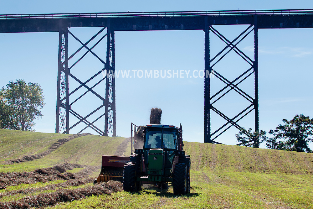 Cornwall, New York - A farmer driving a tractor bales hay in a field by the Moodna Viaduct railroad trestle on Sept. 15, 2015.