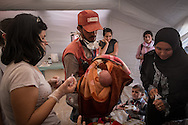Newly arrived Syrian refugees in Turkey recieve vaccinations and a brief medical check before being taken to temporary shelter.