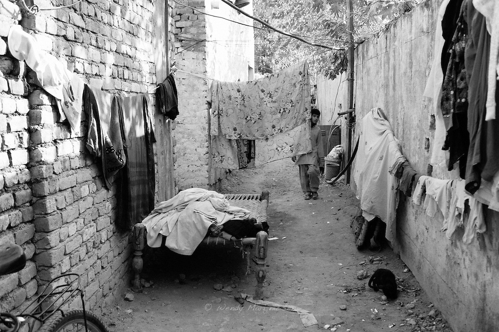 A bed and some washing in one of the alleys of the French colony slum in the city center of Islamabad