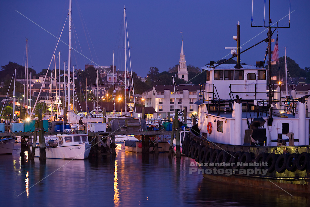 Newport RI . skyline viewed from the state pier in Newport harbor at dusk with lobster boats and a tug boat.