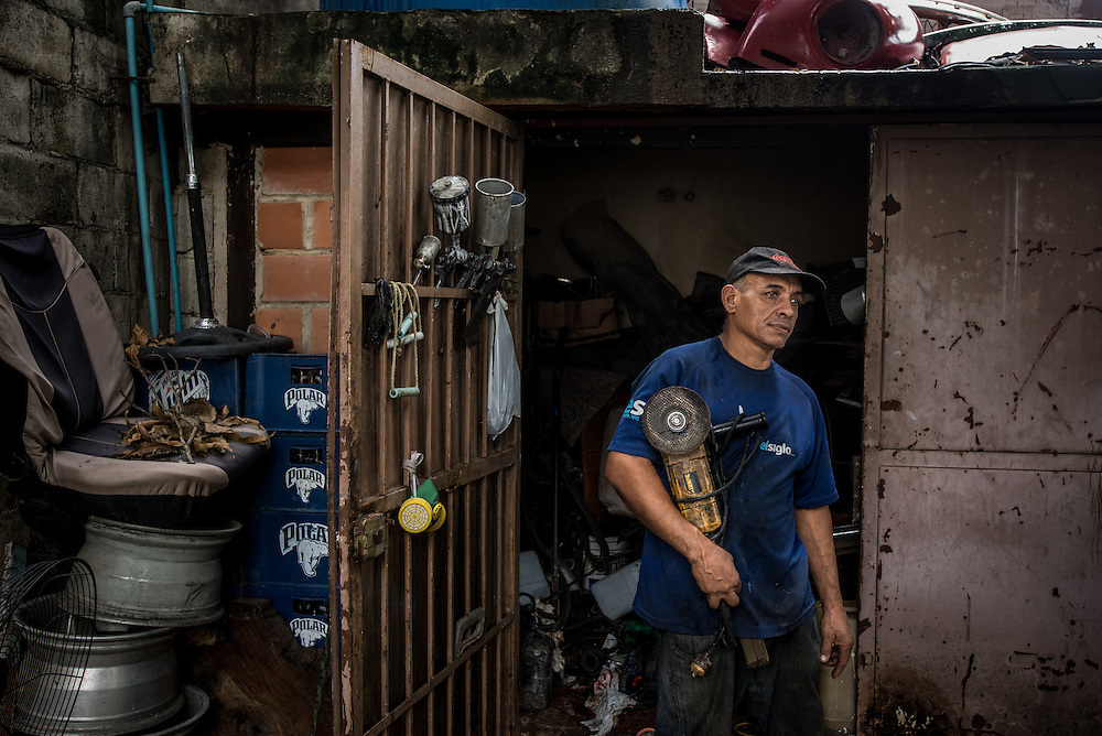 MARACAY, VENEZUELA - JULY 4, 2016: Mario Simeone, 54, poses for a portrait with his electric circular saw, in front of the tool shed that he now has to keep locked at all times with the key hidden - because his schizophrenic son, Accel  tried to cut off his own arm with the saw after going three weeks without the medicines that he needs to control his schizophrenia. The economic crisis that has left Venezuela with little hard currency has already hit its health system, leaving hospitals without antibiotics, surgeons without gloves and patients dying on emergency room tables.  But beyond the hospital wards, thousands more mental health patients—many of whom had been living relatively normal lives at home with their families under medication—are slipping back into relapse for lack of basic psychiatric medications which control their symptoms, medical experts say. PHOTO: Meridith Kohut for The New York Times